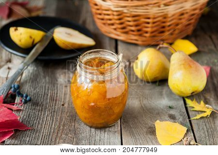 Close Up Pear Jam And Fresh Yellow Ripe Pears On Old Rustic Wooden Table. Autumn Harvest Still Life