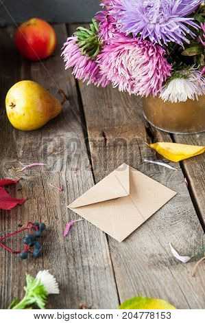 Thanksgiving Background With Seasonal Fruits, Flowers And Craft Paper Envelope On A Rustic Wooden Ta