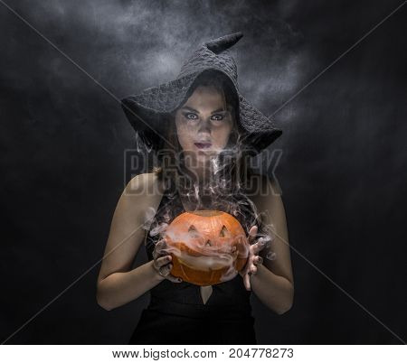 Seious  witch with smoky pumpkin in her hands on black background