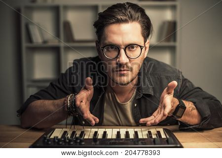 handsome young man in eyeglasses with keyboard controller