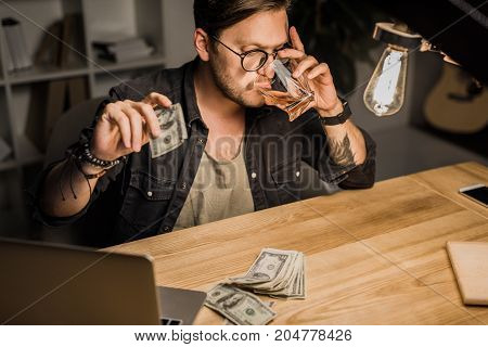 Man Drinking Whiskey With Pile Of Cash
