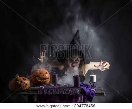 Attractive witch in the wizarding lair with smoke going from her mouth.Halloween.Fairytales
