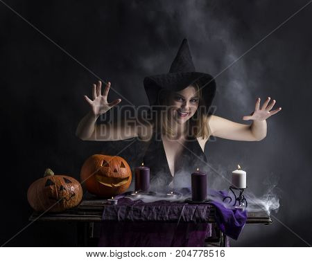 Attractive witch in the wizarding smoky lair.Halloween.Fairytales.