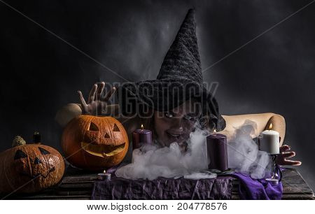 Attractive witch in the wizarding lair with the smoke going from her mouth. Fairytales. Halloween.