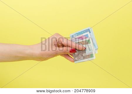 Fifty, Twenty And Ten Zloty In The Woman's Hand, Yellow Background