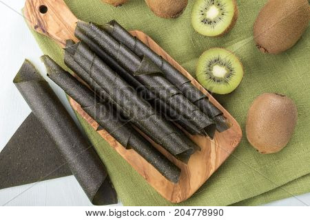 Kiwi fruit leather rolls and fresh fruits. Top view.