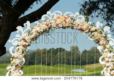 deyails of beautiful wedding arch of flowers and hanging beads on a background green field with trees