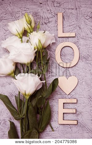 Wooden Letters, and white bouquet on grey wooden background. Romantic holiday concept, top view.