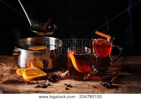 hot steaming mulled wine cooked in a pot and served in glass mugs with Christmas spices like orange slices cloves star anise and cinnamon on a rustic wooden table against a dark background selected focus narrow depth of field