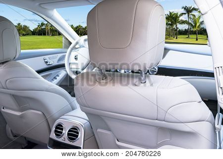 White leather interior of the luxury modern car. Leather comfortable white seats and multimedia. Steering wheel and dashboard. Automatic gear shift. Car interior details