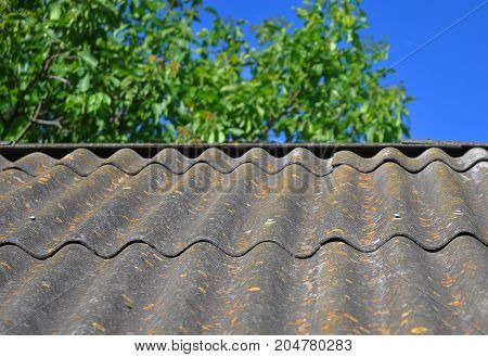 Dangerous asbestos new roof tiles with roof window dormer and small balcony. Use of asbestos in buildings is bad for health.