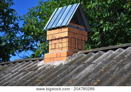 Dangerous asbestos house roof with brick chimney