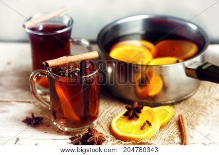 mulled wine in a glass mugs and in a pot with Christmas spices like orange slices cloves star anise and cinnamon on a bright rustic wooden table selected focus very narrow depth of field