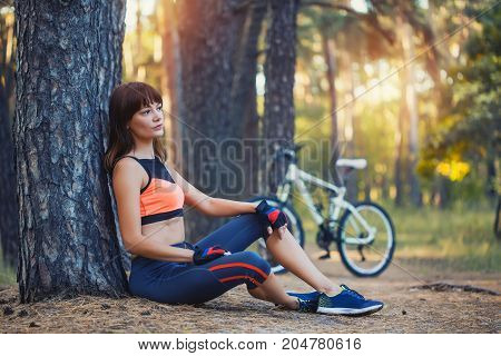 woman Cyclist resting under a tree . Adventure travel.