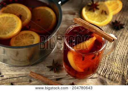 mulled wine in a glass mug and in a pot with Christmas spices like orange slices cloves star anise and cinnamon on a rustic wooden table selected focus very narrow depth of field
