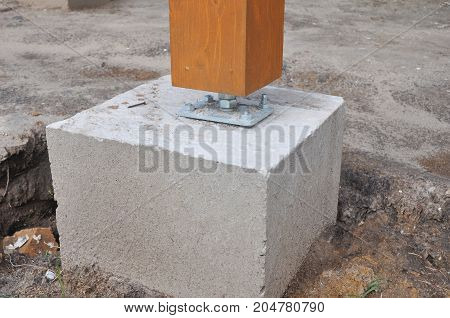 Wooden pillar on the construction site concrete with screw. Wooden Pillar.