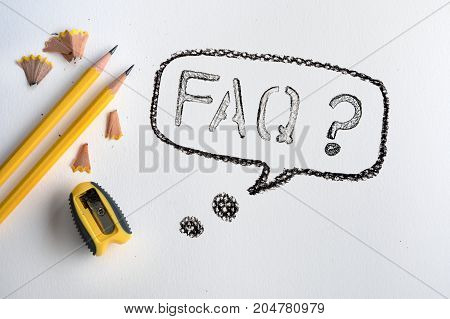 Yellow pencil with shaving on white drawing watercolor paper with FAQ text word creative work tool project