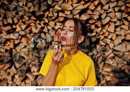 Young Funny Girl With Bright Make-up, Wear On Yellow Shirt Blown Soap Bubbles Against Wooden Backgro