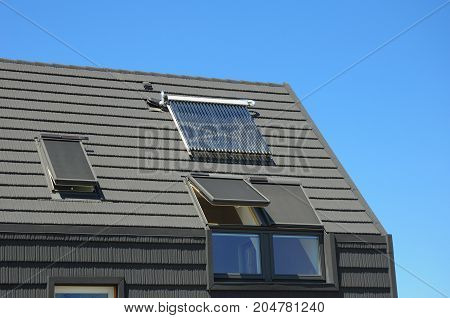Energy Efficiency New Passive House Building Concept. Closeup of Solar Water Panel Heating Dormers Solar Panels Skylights Ventilation and Air Conditioning Systems Installed on Tiled House Roof