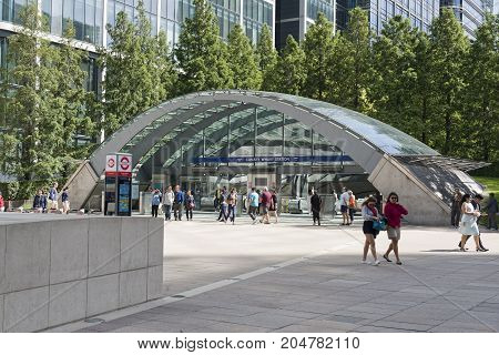 London England - August 13 2017: Canary Wharf underground station Docklands London UK. Modern Architecture with glass and steel arch leading into the station. People enter and leave the station and people walk passed. Tall Buildings are arround the square