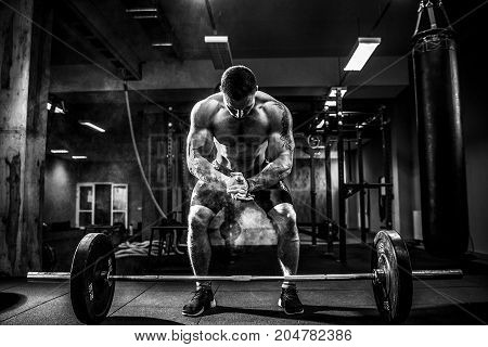 Muscular fitness man preparing to deadlift a barbell over his head in modern fitness center.Functional training.Snatch exercise