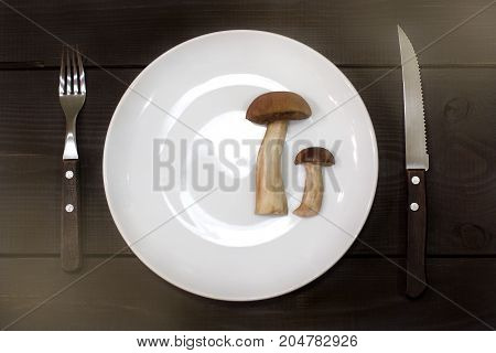 small and large mushroom on a plate next to a knife and fork on a table top view / delicacy dish