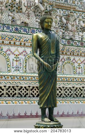 Standing buddha statue in the temple of the dawn Wat Arun in Bangkok