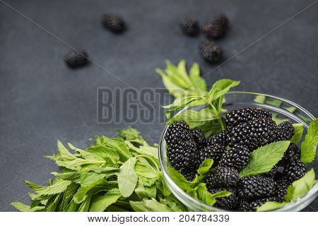 Glass plate with ripe blackberries and green mint leaves on a black surface. Macro photo of ripe blackberries.