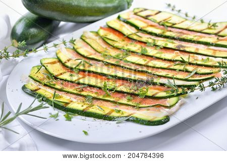 Grilled zucchini slices marinated with olive oil and herbs, served with fine Italian ham on a white platter