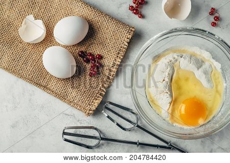 Top view photo of a broken egg on flour in a glass plate. Mixer fits on a white surface. Eggs and currant on a brown bagging. Ingredients for healthy rustic breakfast.