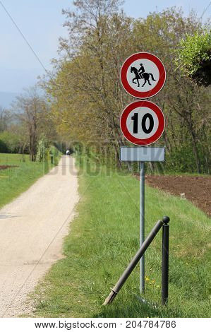 pedestrian street with no access to horses and road sign with speed limit