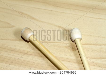 A pair of knitting needles made of wood on neutral background