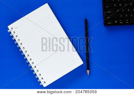 White note book and black pencil and black keyboard on blue color background with copy space.
