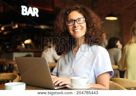 Beautiful woman in cafe with coffee Cup and laptop