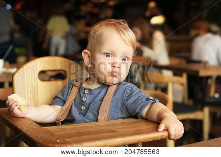 Little boy is sitting in a cafe with a banana