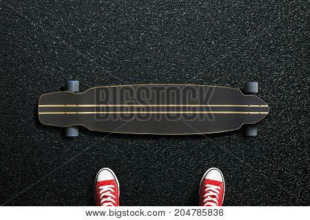 Long skateboard with sneakers on the asphalt road