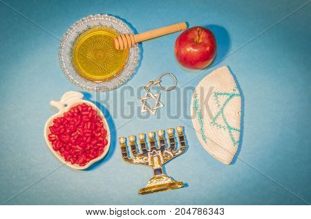 The Jewish New Year Rosh Hashanah concept - apple shaped plate with red pomegranate seeds, plate with honey, apples and David Star on a blue background. Rosh Hashanah greeting