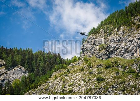 Army helicopter preforming a rescue in the mountains. Hovering chopper is attending in mountain accident over Komarca in Slovenia.