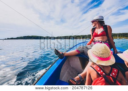 Mother And Daughters In A Boat On The Sea.