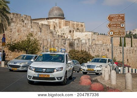 JERUSALEM, ISRAEL. September 15, 2017. Israeli taxi cab car in front of the Dung gate of the Old city of Jerusalem. With the gray dome of the Al Aqsa mosque seen on the background.