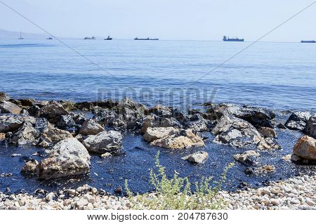 Oil spill. Environmental disaster. Beach with rocks is covered with a layer of oil.