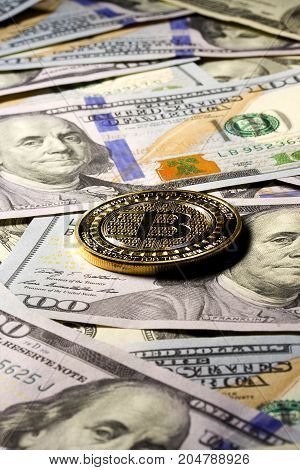 Internet currency Coin Bitcoin on the background of lying one hundred dollar bills