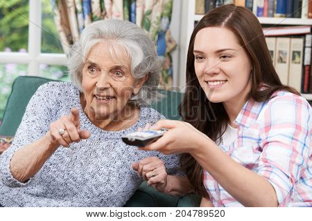 Teenage Granddaughter Watching Television With Grandmother At Home