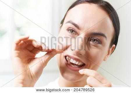 Head And Shoulders Shot Of Woman Flossing Teeth In Bathroom