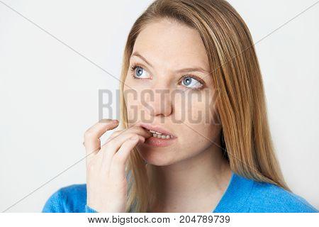 Studio Shot Of Nervous Woman Biting Nails