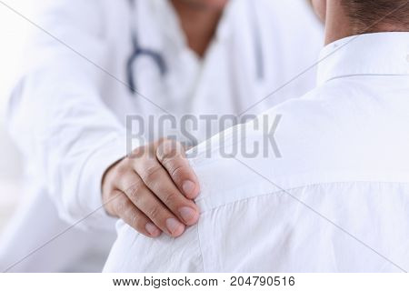 Friendly Male Doctor Hold Patient Shoulder In Office During Reception
