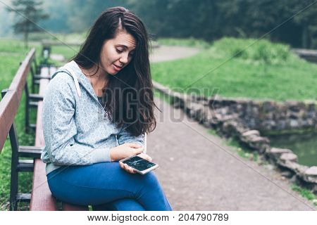 sad woman sitting on the bench with cracked phone