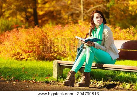 Woman Reading Book Sitting On Bench In Park