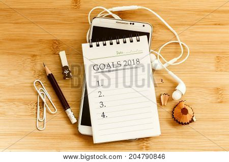 notepad with pencil and smart phone for setting GOALS 2018 new year plan concept overhead shot or Top view
