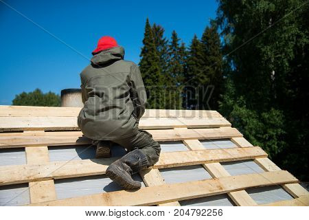 Worker on a renovation roof under construction, carpenter on the work.